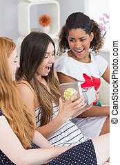 Cheerful young women surprising friend with a gift on sofa...