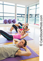 Sporty fitness class doing sit ups on exercise mats - Side...