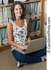 Smiling student against bookshelf with laptop on the library floor