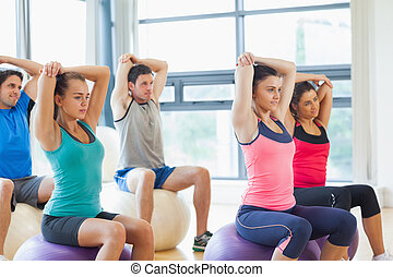 Sporty people stretching hands on exercise balls at gym -...