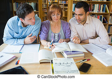 Adult students studying together in the library - Three...