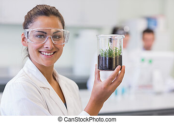 Smiling female scientist analyzing a young plant at lab