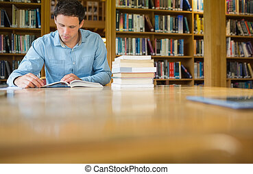 Serious mature student studying at library desk - Serious...