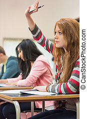 Female student raising hand by others in classroom - Side...