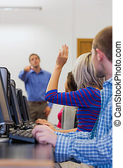 Teacher explaining to students in computer room