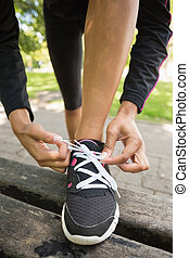Close up low section of sporty woman wearing shoes in park -...