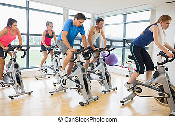Determined people working out at spinning class - Determined...