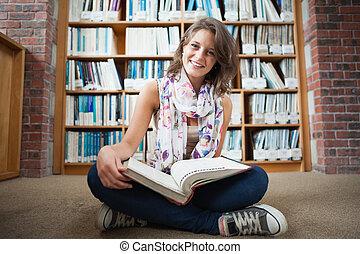 Happy female student against bookshelf - Full length of a...