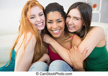 Portrait of happy female friends embracing each other -...