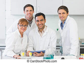 Smiling scientists with tablet PC in the lab - Group...