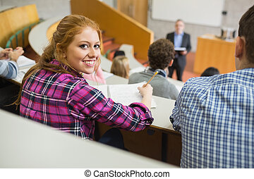 Smiling female with students and teacher in lecture hall -...