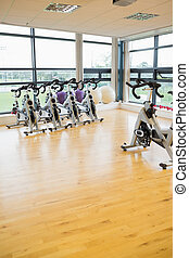 Spinning exercise bikes in gym room