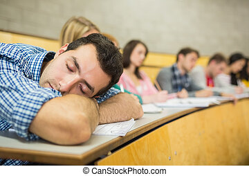 Male sleeping with students in lecture hall - Male sleeping...