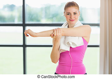 Woman with towel around neck stretching hand in fitness...