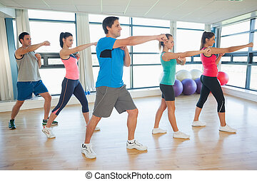 Sporty people doing power fitness exercise at yoga class -...