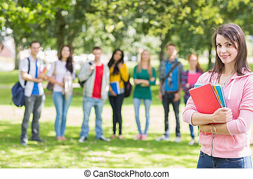 College girl holding books with students in park - Portrait...