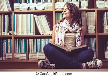 Thoughtful female student sitting against bookshelf with a book on the library floor