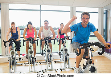 Happy man teaches spinning class to four people - Portrait...