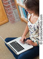 Student against bookshelf using laptop on the library floor...