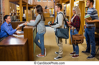 Students in a row at the library counter - Side view of...