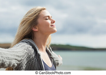 Side view of young woman stretching her arms on beach - Side...