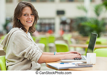 Female student using laptop at cafeteria table