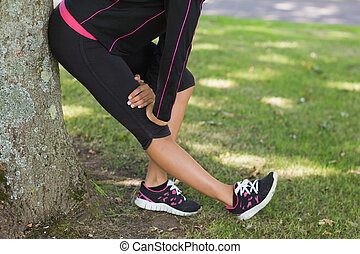 Low section of woman stretching her leg during exercise at...
