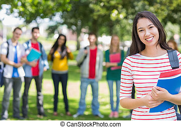 College girl holding books with blurred students in park -...
