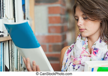 Female student with books by the shelf in library - Close-up...