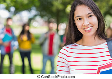 Close-up of college girl with blurred students in park -...