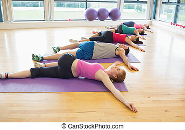 Full length of sporty people stretching on mats at yoga...