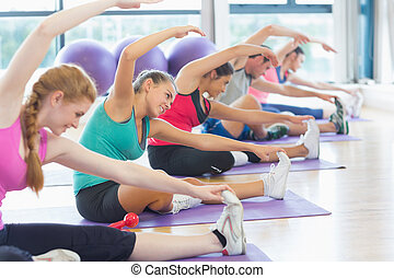 Fitness class and instructor doing stretching exercise -...