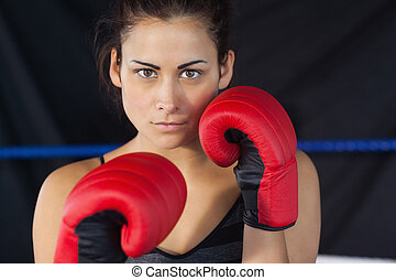 Close-up portrait of a beautiful woman in red boxing gloves...
