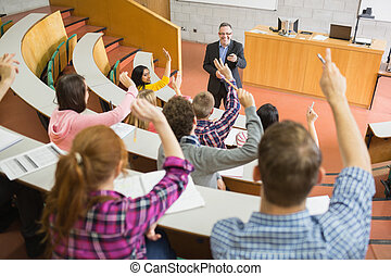 Students raising hands with teacher in the lecture hall -...