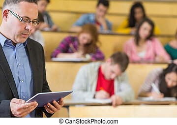 Teacher using tablet PC with students at lecture hall -...