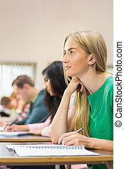 Young students writing notes in classroom - Side view of a...