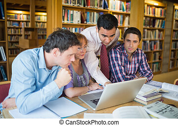 Mature students with teacher and laptop in library - Mature...