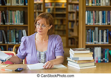 Mature female student studying at desk in the library -...