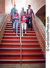 College students walking down stairs in college - Full...
