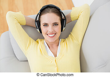 Woman listening music through headphones on sofa - Smiling...