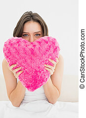Woman holding heart shaped pillow in bed