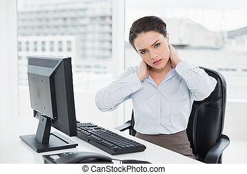Businesswoman with neck pain sitting at office - Portrait of...