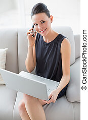Beautiful smiling well dressed young woman using laptop and...
