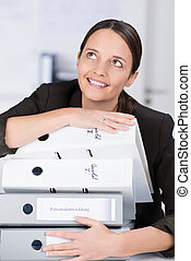 Smiling businesswoman with a stack of files - Smiling...