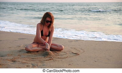 Woman building sand castle on beach