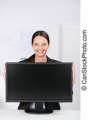Smiling businesswoman with a wide screen monitor - Smiling...