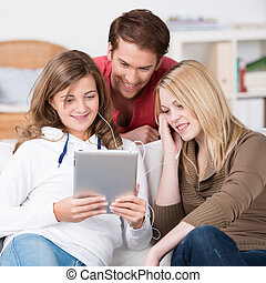 Teenage friends listening to music on a tablet-pc grouped...