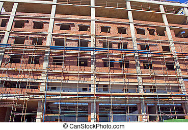 scaffolding erected around brick and concrete building under...