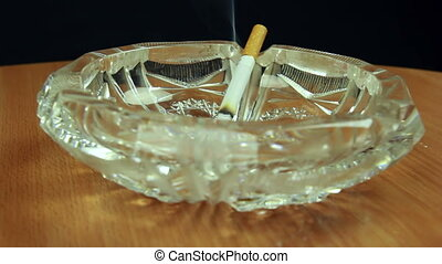 Smoking cigarette in ashtray dolly shot front view
