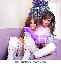 Opening Christmas present - Young brunette mother with teen...
